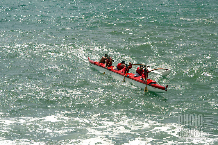 A six-man crew competes in an outrigger canoe race in open ocean off of the coast of Kaua'i.