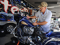 NWA Democrat-Gazette/ANDY SHUPE<br /> Royce Holley of Philadelphia, Miss., a worker with Monster Brite LEDs of Atlanta, installs LED lighting Wednesday, Sept. 23, 2015, on an Indian motorcycle owned by Carl Sears of Bella Vista at the 16th annual Bikes, Blues & BBQ motorcycle rally at the Baum Motorcycle Village at Baum Stadium in Fayetteville.