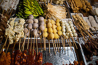 Shaokao, or barbecue, ingredients wait on skewers for diners at a streetside restaurant near Shibati, or 18 Steps, in central Yuzhong district in Chongqing, China. Patrons choose skewers of vegetables, tofu, mushrooms, and meat, which the cook barbecues and then mixes together with spices. In the center, there are whole peeled potatos on skewers. In most of the rest of China, the potatos are usually thinly sliced for shaokao.