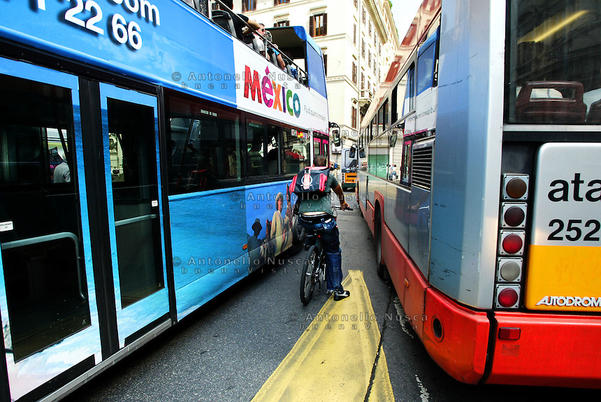 Un ciclista intrappolato nel traffico della città in una strada del centro storico.