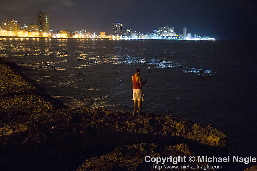 HAVANA, CUBA -- MARCH 24, 2015:   A man fishes along the Malecon in Havana, Cuba on March 24, 2015. Photograph by Michael Nagle