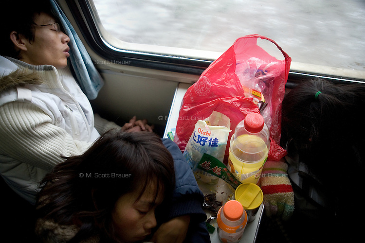 Passengers try to sleep in a crowded train car on the way from Nanchang to Guilin, China.  The 14-hour trip eventually took 27 hours, with many delays.  In late January and early February 2008 some of the worst storms in 50 years crippled the Chinese transportation infrastructure during the annual Spring Festival and Lunar New Year holidays, a traditionally heavy travel period; roads jammed up or were closed, cities lost power for days at a time, and the trains quit running throughout the region.  The Chinese government issued a plea to citizens not to return to their homes for the holidays.