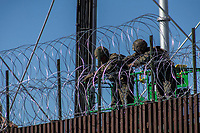 "MEXICALI,  MEXICO - November 26. US Army soldiers are seen from the mexican side fortifying US-Mexico border fence with barbed wire on November 26, 2018 in Mexicali, Mexico.<br /> The U.S. government said it was starting work to ""harden"" the border crossing  Mexico, to prepare for the arrival of a migrant caravan leapfrogging its way across western Mexico. For the Trump administration and those who support the president's hard-line stance on illegal immigration, the chaos illustrated what they long have feared. For others, the images of the Border Patrol using tear gas on a group of migrants that included children were deeply disturbing<br /> (Photo by Luis Boza/VIEWpress)"