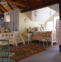 The master bedroom has a simple painted bed covered in vintage textiles under the eaves
