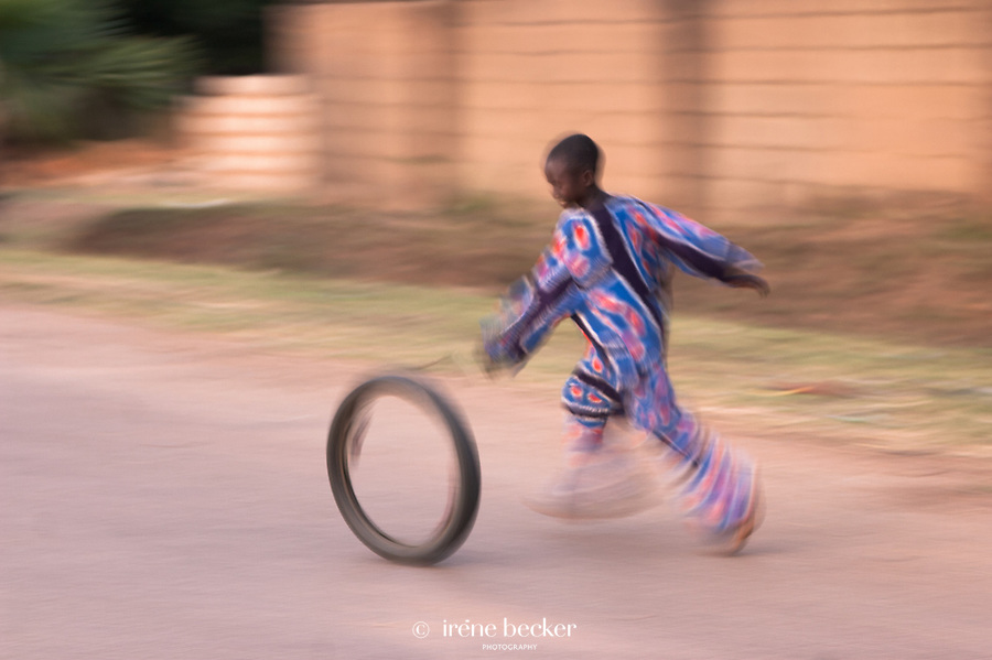 Boy playing with an old bicycle tire. One of the oldest games in the world