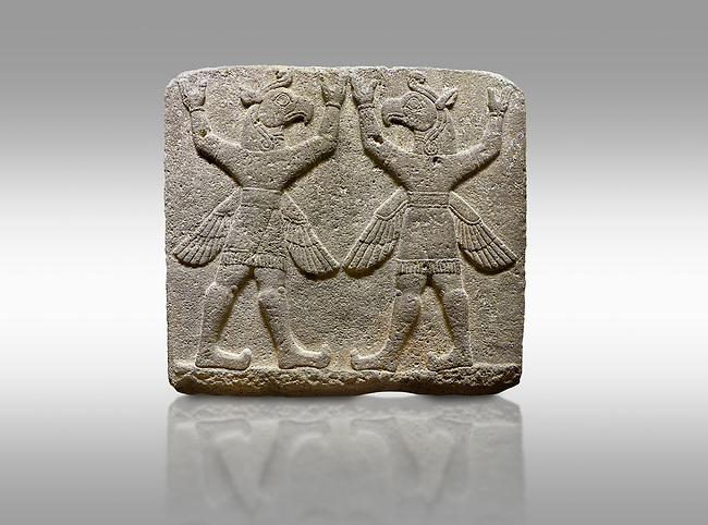 """Hittite relief sculpted orthostat stone panel of Herald's Wall Basalt, Karkamıs, (Kargamıs), Carchemish (Karkemish), 900-700 B.C. Bird-headed, winged figures of human body. Anatolian Civilisations Museum, Ankara, Turkey.<br /> <br /> These figures are called as """"Winged Griffin Demons"""". Embossing is constructed symmetrically. Their hands are on their heads. It is assumed that they carry the heavens."""