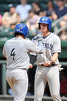 Catcher Jose Briceno (4) of the Asheville Tourists is congratulated by Ryan McMahon after scoring a run in a game against the Greenville Drive on Sunday, July 20, 2014, at Fluor Field at the West End in Greenville, South Carolina. Briceno is the No. 29 prospect of the Colorado Rockies, according to Baseball America. Asheville won game one of a doubleheader, 3-1. (Tom Priddy/Four Seam Images)