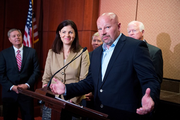 UNITED STATES - MAY 14: Eric Brandenburg, who received a Silver Star while serving in the U.S. Air Force, speaks at a news conference in the Capitol Visitor Center to oppose the deactivation of the A-10 fighter aircraft, May 14, 2014. Also appearing from left are, Sens. Lindsey Graham, R-S.C., Kelly Ayotte, R-N.H., Johnny Isakson, R-Ga., and Saxby Chambliss, R-Ga. (Photo By Tom Williams/CQ Roll Call)