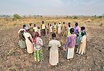 Members of the United Methodist Women in Yei, Southern Sudan, pray in a circle after working together to prepare a plot of land for planting vegetables--all part of a food security project for the group. Many of them widows, the women live precariously but at peace after having returned from refugee camps in neighboring Uganda and the Congo in recent years. A 2005 Comprehensive Peace Agreement laid the foundations for peace in Sudan's south after decades of war. NOTE: In July 2011, Southern Sudan became the independent country of South Sudan