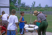 A child watches attentively while others help a ranger demonstrate how the Breeches Buoy was rigged at the Glen Haven Life Saving Station Museum in Slleping Bear Dunes National Lakeshore in Leelanau County, Michigan