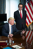 US President Donald J. Trump (L), with Secretary of Treasury Steven Mnuchin (R) reads a financial services Executive Order prior to signing during a ceremony in the US Treasury Department building in Washington, DC, USA, 21 April 2017. President Trump is making his first visit to the Treasury Department for a memorandum signing ceremony with Secretary Mnuchin.<br /> Credit: Shawn Thew / Pool via CNP