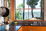 A corner of windows with a water view in the kitchen of a contemporary island home.  This image is available through an alternate architectural stock image agency, Collinstock located here: http://www.collinstock.com