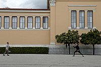 Pictured: Two men play with rackets outside the Zappeio Mansion.<br /> Re: Police patrol the streets to enforce the measures of self-isolation in an effort to fight the Coronavirus Covid-19 pandemic in Athens, Greece.