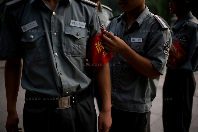 Park security guards fasten government sashes on their arms before work in Beijing, China on Tuesday, August 12, 2008.  Kevin German