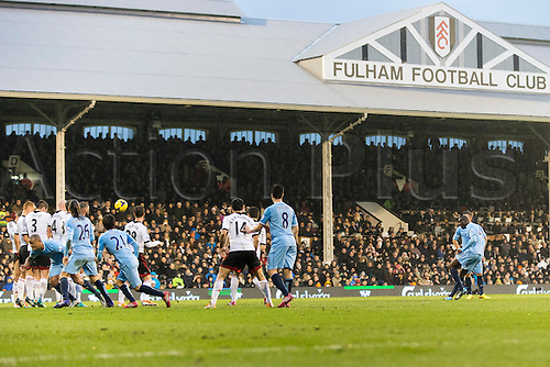 21.12.2013 London, England. Manchester City's Yaya TOURE scores the opening goal from a free-kick during the Premier League game between Fulham and Manchester City from Craven Cottage.