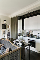 The apartment is a combination of vintage furnishing, eye-catching fabrics and masterly use of space. In the sitting room at console table stands behind a sofa upholstered in grey check fabric. A set of mirrored folding doors cleverly conceals a kitchenette.