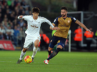 (L-R) Ki Sung Yueng of Swansea against Olivier Giroud of Arsenal during the Barclays Premier League match between Swansea City and Arsenal at the Liberty Stadium, Swansea on October 31st 2015