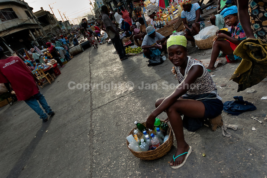A Haitian woman sells bottled drinks in the La Saline market, Port-au-Prince, Haiti, 21 July 2008. Every day thousands of women from all over the city of Port-au-Prince try to resell supplies and food from questionable sources in the La Saline market. The informal sector significantly predominate within the poor Haitian economics and the regular shops virtually do not exist. La Saline is the largest street market area in Port-au-Prince.