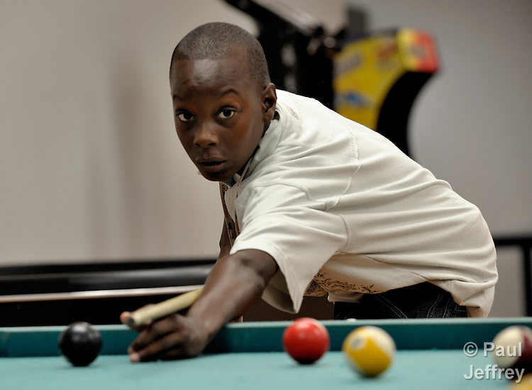 A boy plays pool in the Mary E. Brown Center, part of the Lessie Bates Neighborhood House in East St. Louis, Illinois.