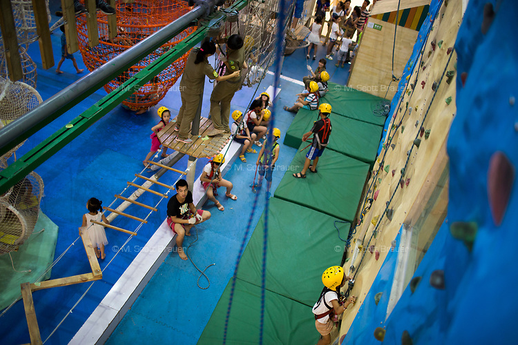 Children play in an obstacle course and climbing wall in a mall in Xian, Shaanxi, China.