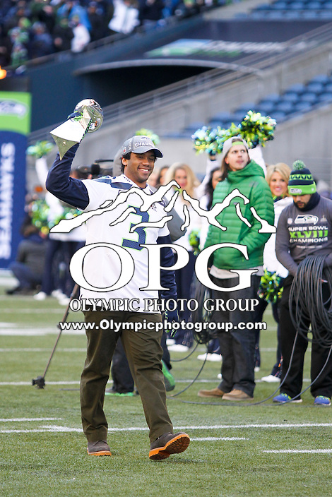 2014-02-05:  Seattle Seahawks quarterback Russell Wilson carried the Super Bowl trophy onto the field.  Seattle Seahawks players and 12th man fans celebrated bringing the Lombardi trophy home to Seattle during the Super Bowl Parade at Century Link Field in Seattle, WA.