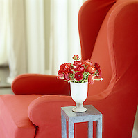 Close up of a bunch of red ranunculus on a tall side table beside a red slip-covered wing-backed armchair