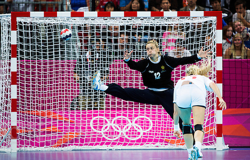 11 AUG 2012 - LONDON, GBR - Sonja Barjaktarovic (MNE) of Montenegro (left, in black) fails to save a shot from Linn Jørum Sulland (NOR) (right) of Norway during the women's London 2012 Olympic Games handball final at the Basketball Arena in the Olympic Park, in Stratford, London, Great Britain (PHOTO (C) 2012 NIGEL FARROW)