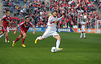 New York defender Brandon Barklage (25) shoots the ball in front of Chicago midfielder Daniel Paladini (11).  The Chicago Fire defeated the New York Red Bulls 3-1 at Toyota Park in Bridgeview, IL on April 7, 2013.