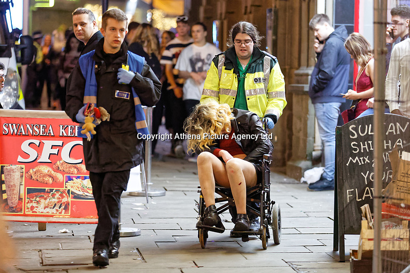 Pictured: A woman is taken a way in a wheelchair by a St John Ambulance member of staff in Wind Street, Swansea. Monday 31 December 2018 and Tuesday 01 January 2019<br /> Re: New Year revellers in Wind Street, Swansea, Wales, UK