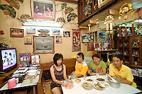 "Thailand. Bangkok. The family Saengurai sits at the table in her rented house. The family is afraid of losing their home because of a development master plan of the Bangkok Metropolitan Administration (BMA). The family of chinese origin has been living in Tha Tian in a shophouse for generations. Food on table and television.  A picture of King Bhumibol is taped on the wall. Bhumibol Adulyadej (born 5 December 1927), is the current King and Head of the State of Thailand. Publicly acclaimed ""the Great"" he is also known as Rama IX. Having reigned since 9 June 1946, he is the world's longest-serving current head of state and the longest-serving monarch in Thai history. Tha Tian is a community located in the downtown area and in the center of the urban historic district, called Koh Rattanakosin. 02.04.09 © 2009 Didier Ruef"