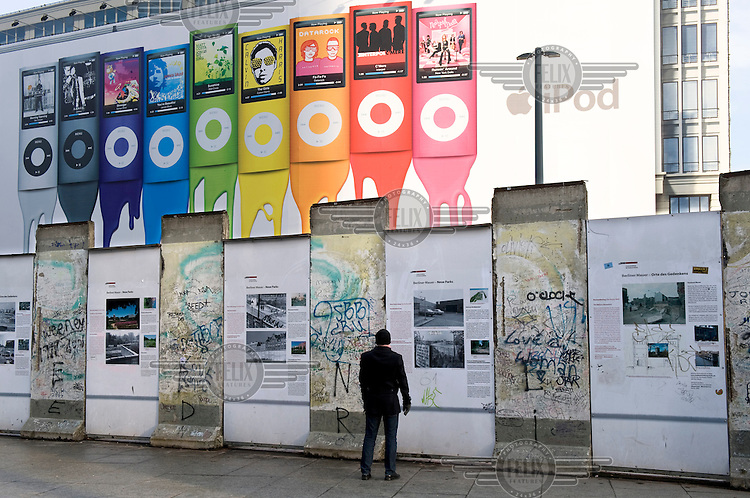Tourist at the remains of the Berlin Wall at Potsdamer Platz, with a large Apple iPod advert in the background.
