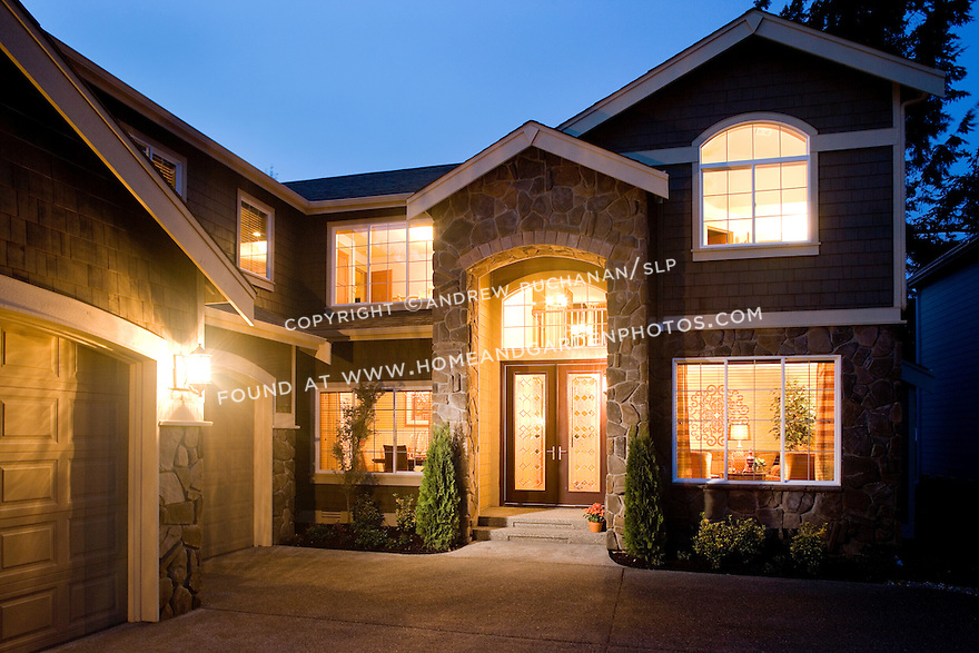 A large, two story, 2-story,4+ BR bedroom builder spec contemporary home in the suburbs surrounding Seattle, WA, glows with a warm, welcome glow in this evening dusk image as a deep blue sky shines behind.
