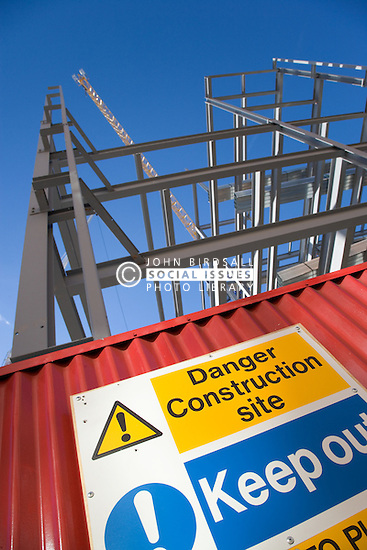 Looking up through the girder framework of the new Litmus project building and showing a danger warning sign at ground level, In the city of Nottingham,