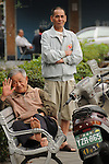 Kaohsiung, Taiwan -- Spectators at a traditional Taiwanese hand puppet theater performance at a roadside park in Kaohsiung.