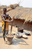 Kipili, Tanzania. Smiling girl pounding cassava in a wooden bowl with pestle stick.