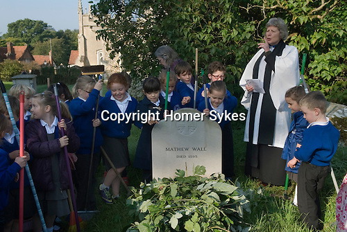 Old Mans Day, Braughing, Hertfordshire UK. October 2nd. 2015. The vicar the Rev'd Julie Gawthrope with  children from Jenyns First School around the grave of Mathew Wall. Brambles have been placed on the grave as directed in his will to prevent cattle grazing over it. A short service is held while the church bells tolled for a funeral, and then a wedding peal is rung.
