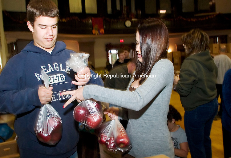 NAUGATUCK, CT- 18 NOV 2007- 111807JT02- <br /> Chris Swasey, 15, and Julie Longo, 15, students at Naugatuck High School, organize apples during a basket stuffing event by the Ecumenical Food Bank at St. Michael's Church in Naugatuck on Sunday.<br /> Josalee Thrift / Republican-American