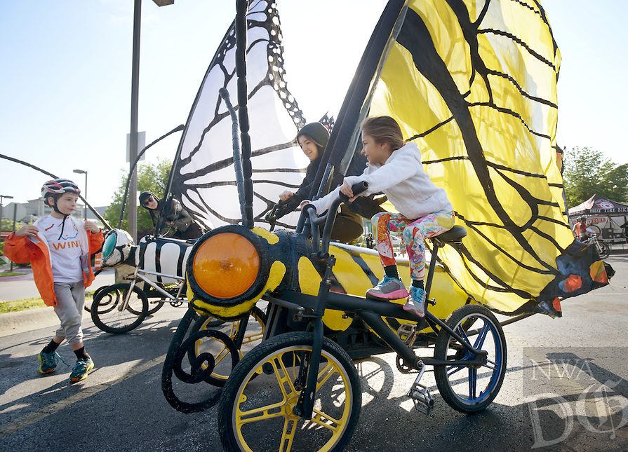 NWA Democrat-Gazette/BEN GOFF @NWABENGOFF<br /> Sophia Calico, 6, from Bentonville, takes a ride with Rachel Rosen with the Bike Zoo from Austin, Texas, on one of the Bike Zoo butterfly bikes on Saturday May 14, 2016 at the starting area for the spring Square 2 Square bike ride in downtown Fayetteville. Participants in the ride traveled 32 miles from downtown Fayetteville to downtown Bentonville on the Razorback Regional Greenway, with festivities along the way and at the finish. The Bike Zoo was offering rides on a variety of creative pedal-powered animals at stops along the greenway.
