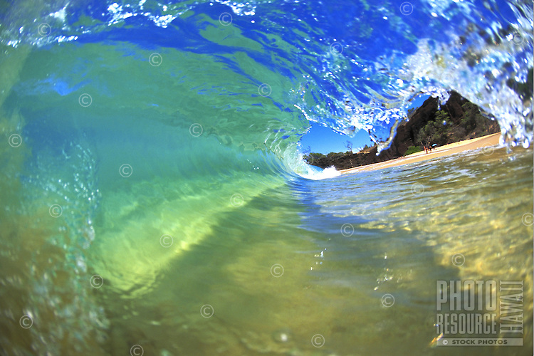 Clean, clear small wave with sandy bottom and blue skies to enhance water color.  Makena, Maui.