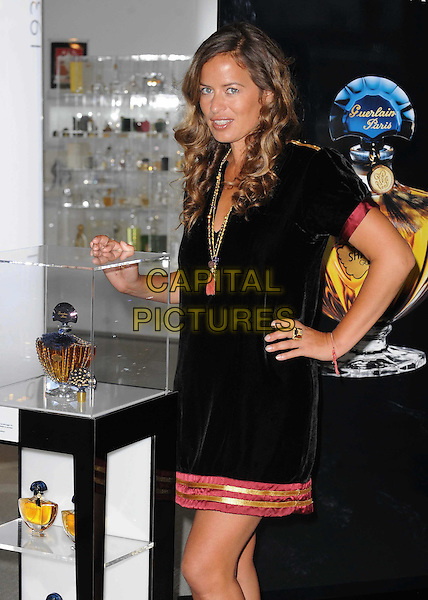 JADE JAGGER.Launches her Shamilar Eau De Parfum bottle at Harrods, Knightsbridge, London, England, UK, .September 8th, 2010..photocall half length black gold necklace tassel  red trim trimmed velvet dress hand on hip  .CAP/WIZ.© Wizard/Capital Pictures.