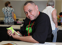 New York, NY, USA - June 25, 2011: Freddie Burgos, Origami folder at the OrigamiUSA Convention in New York City holding a rat he folded that was designed by Eric Joisel