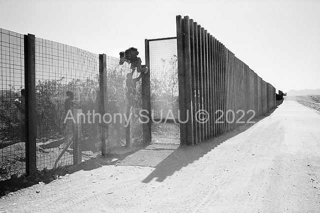 Naco, Arizona.May 4, 2008..West of Naco illegal immigrants scale the new 12 foot fence. Among them are women and a 10 year old boy. ..The vast majority of the Arizona/Mexican border is now marked by vehicle barrier or high fencing. Also a graded road runs along the majority of this new fencing.