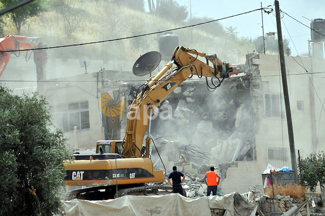 Israeli bulldozers destroy a home in the neighborhood of al-Tur in Israeli-occupied east Jerusalem on May 21, 2013, in implementation of a court order which ruled that the house was built without a municipality permit. Photo by Sliman Khader