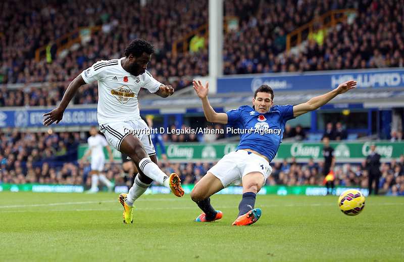Liverpool, UK. Saturday 01 November 2014<br /> Pictured L-R: Wilfried Bony of Swansea takes a shot at goal but fails to score, against him is Gareth Barry of Everton.<br /> Re: Premier League Everton v Swansea City FC at Goodison Park, Liverpool, Merseyside, UK.