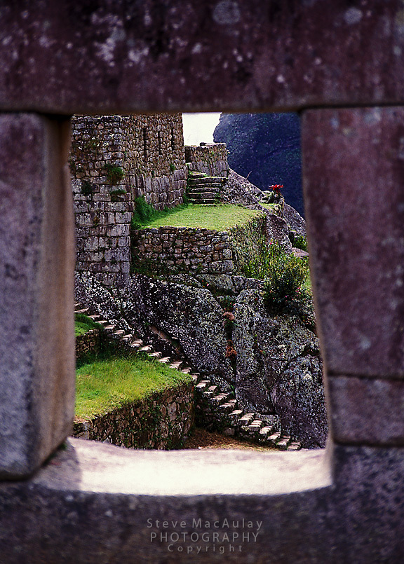 View through carved and stacked stone window of stairway beyond, Machu Picchu, Peru