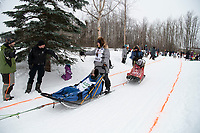 Junior Iditarod Champion Nicholas Sousa and team run past spectators on the bike/ski trail near University Lake with an Iditarider in the basket and a handler during the Anchorage, Alaska ceremonial start on Saturday, March 7 during the 2020 Iditarod race. Photo © 2020 by Ed Bennett/Bennett Images LLC