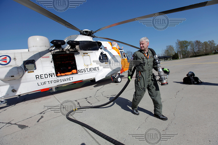 Anesthesiologist Hallstein Sørebø refueling the helicopter. Crew from Norwegian Air Force 330 squadron, flying Westland Sea King helicopter. The core mission of the squadron is SAR (search and rescue), but they also fly HEMS (Helicopter Emergency Medical Service), complementing the civilian air ambulance service.<br /> This crew fly out of Rygge Air Station, Norway.