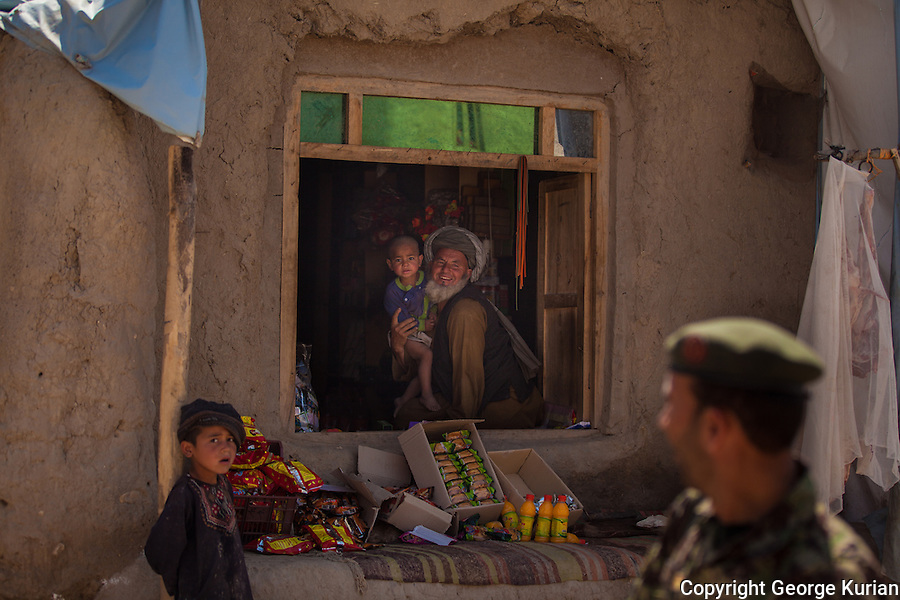 An Afghan soldier is greeted by a shopkeeper in Qaragholi.