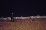 © Joel Goodman - 07973 332324. 26/09/2017. Brighton, UK. A nightclub security man checks on the welfare of people on the beach . Revellers at the end of a night out in Brighton during Freshers week , when university students traditionally enjoy the bars and clubs during their first nights out in a new city . Photo credit : Joel Goodman