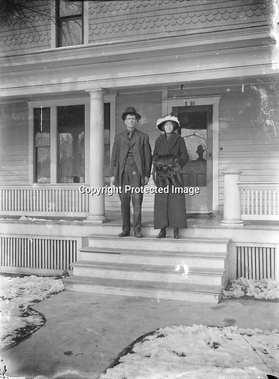 WINTER PORCH POSING. This young couple appears ready to step out on a wintry day. Presumably they found their way back home, despite the fact their address had lost one digit. That address could match numerous houses in Lincoln and the location has not been identified. The full-height Tuscan porch column and the cut shingles decorating the upper wall indicate a house that was built at the dawn of the 20th century.<br />